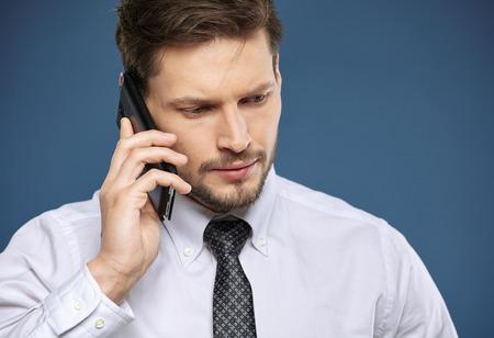 businessman phone: Cool businessman talking on mobile phone