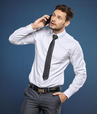 cool man: Cool businessman talking on mobile phone