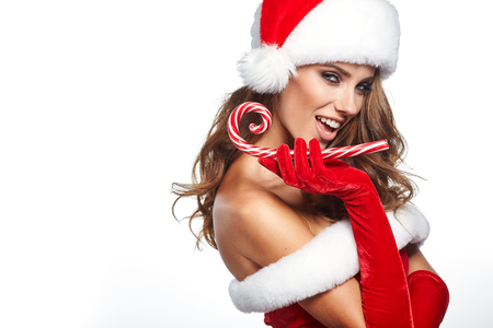 christmas costume: Beautiful woman with santa costume holding red-white Christmas Lollipop