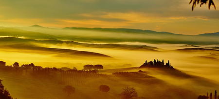 Scenic Tuscany landscape panorama with rolling hills and harvest fields in golden morning light