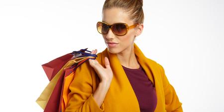 overcoat: Woman wearing autumn overcoat holding shopping bag.
