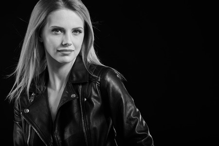 blonde woman: black and white fashion photo of beautiful woman with luxurious curly hair in elegant jacket posing in studio Stock Photo