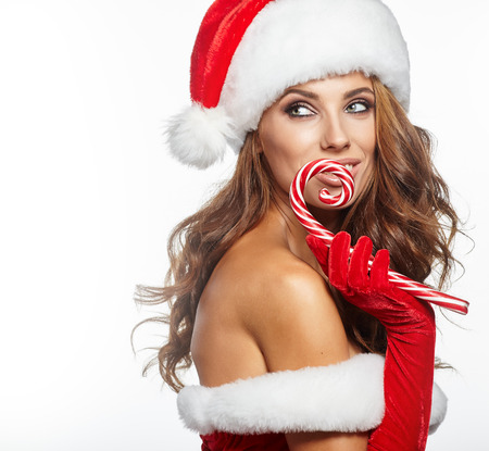 female christmas: Beautiful woman with santa hat holding red-white Christmas Lollipop