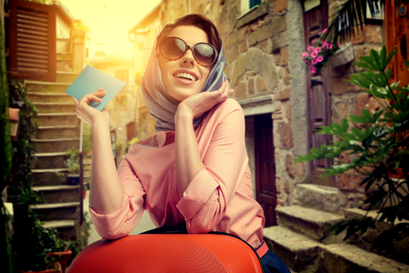 italy street: Elegant woman with a suitcase travel and ticket on street of italian city Stock Photo