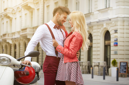young couple smiling: Young funny pretty fashion vintage hipster couple having fun outdoor on the street in summer.