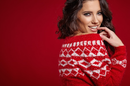 sweater girl: Beautiful girl  in a red sweater with white ornaments stands near a red background
