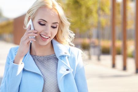 sidewalk talk: Beautiful girl talking on the phone on the autumn street