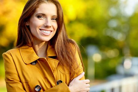 sonriente: Hermosa mujer de pie en un parque en otoño