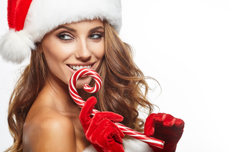 Expressive sexual girl in Santa Claus costume posing with lollipop over white background. Christmas.