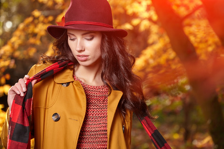 bright colors: Beautiful elegant woman standing in a park in autumn Stock Photo