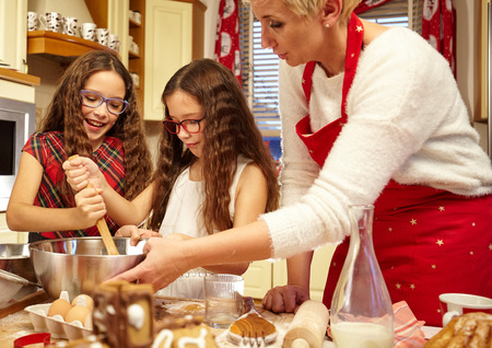 twin sister: Family preparing christmas gingerbread in the kitchen