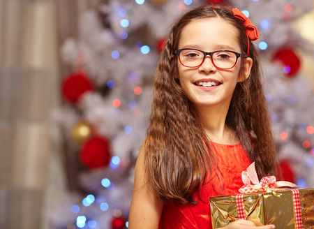glasses eye: Happy sisters holding gifts in front of christmas tree Stock Photo