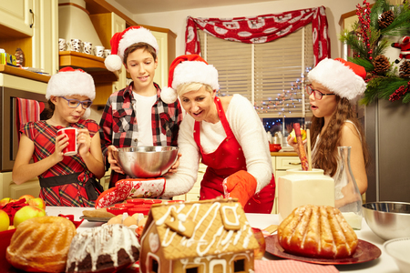 kitchen aprons: Happy christmas family preparing a cake Stock Photo