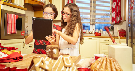 christmas cooking: Twin sisters in santa hats browsing on a tablet
