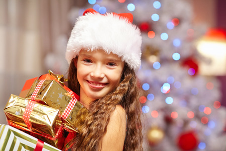 surprise box: Young girl smiling with presents in front of christmas tree