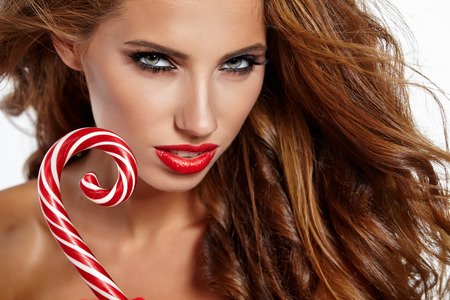 red and white: Beautiful christmas woman holding red - white  Lollipop