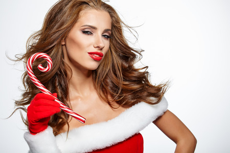 christmas woman: Beautiful christmas woman holding red - white  Lollipop