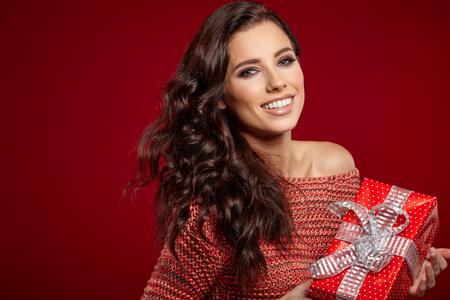 christmas shopping: Beautiful woman portrait hold gift in christmas color style on red background. Stock Photo