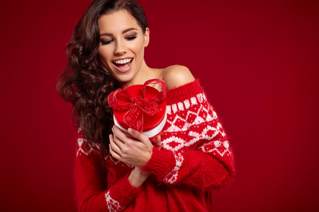 Beautiful woman portrait hold gift in christmas color style on red background. Standard-Bild