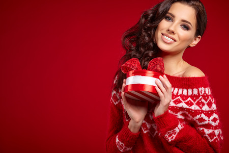 female christmas: Beautiful woman portrait hold gift in christmas color style on red background. Stock Photo
