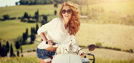 Portret van zomer meisje op scooter - Outdoor op Toscane hiills.Retro schot. Vintage foto