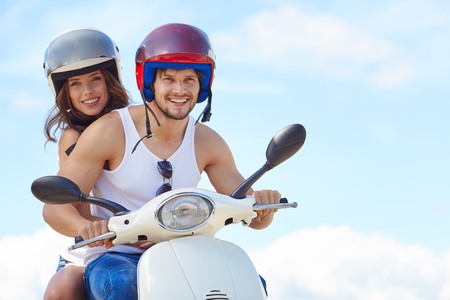 couple having fun: Beautiful young couple in love enjoying and having fun riding on a scooter in a beautiful nature