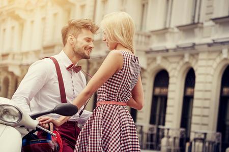 Pareja joven divertida moda vintage bonito inconformista que se divierten al aire libre en la calle en verano.