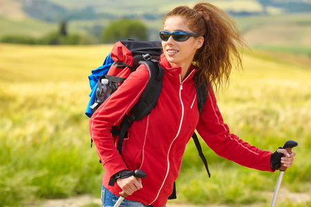 Young backpacker traveling along Italy, female walking in the Tuscany, summer vacation concept