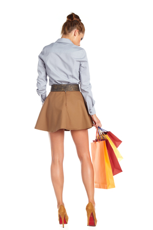 women legs: Shopping woman holding bags, isolated on white studio background. Stock Photo