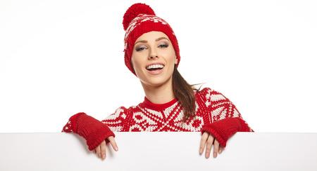 billboard background: Woman in winter dress holding a blank billboard, white background, copyspace
