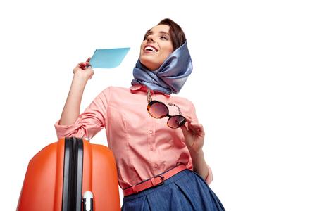valise voyage: jolie femme en rouge avec le sac de Voyage. Modèle féminin studio de fond isolé.
