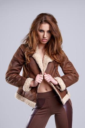 fashion winter: girl wearing winter fur jacket  posing over grey