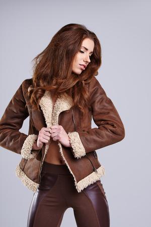 ladylike: girl wearing winter fur jacket  posing over grey