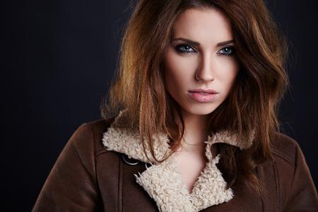 luxuriant: girl wearing winter fur jacket  posing over grey