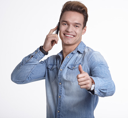 adult  male: smiling young man talking on the phone. Isolated on white background