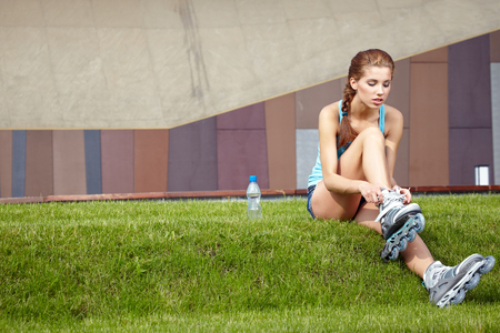 inline: Woman skating in city. Girl going rollerblading sitting in grass putting on inline skates.