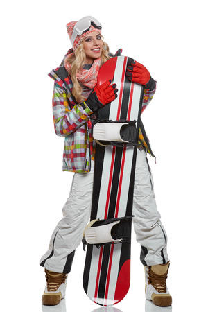 white winter: model wearing snowboard suit holding a snowboard in studio