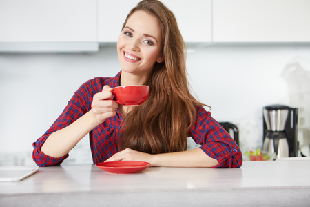 women smiling: young woman drinking coffee at home in the morning Stock Photo