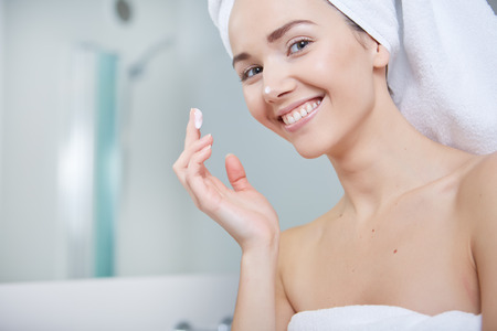 handbasin: Young Woman Wrapped with Bath Towels, Applying Cream on her Face After a Shower at the Bathroom. Stock Photo