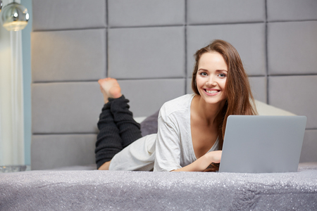 beautiful feet: A smiling woman lying down the bed in front of her laptop