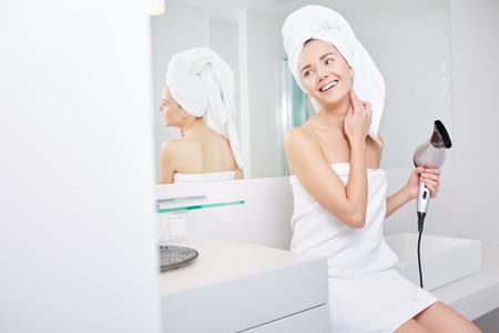 Femme dans la salle de bain avec sèche-cheveux à la main