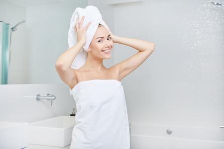 aseo: Fresco joven envuelta en toallas después del baño, sonríe en la cámara