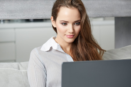 girl with laptop: Woman using a laptop while relaxing on the couch Stock Photo