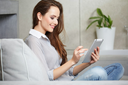 young beautiful woman: Woman using a laptop while relaxing on the couch Stock Photo