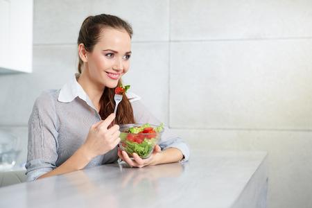 niña comiendo: Beautiful Young Woman Eating Vegetable Salad .Dieting concept.Healthy Food Foto de archivo