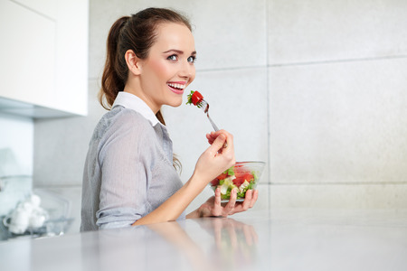 domiciles: Casual brunette posing while eating salad and holding a mixed salad dish