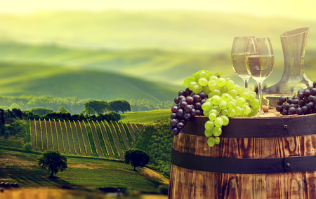 White wine bottle and wine glass on wodden barrel. Beautiful Tuscany background
