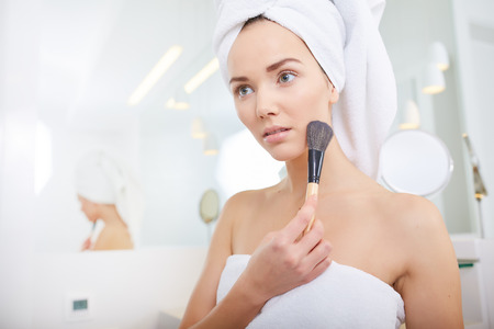 make up brush: A picture of a young woman applying face powder in the bathroom