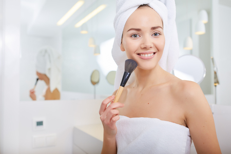 female beauty: A picture of a young woman applying face powder in the bathroom