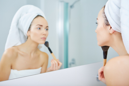 young woman face: Beautiful young woman applying powder on her face Stock Photo